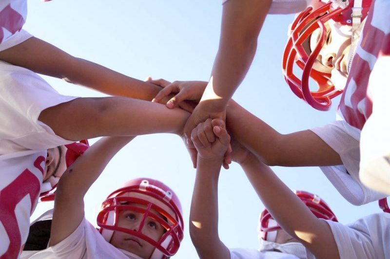 Young football players in a huddle with hands in the middle