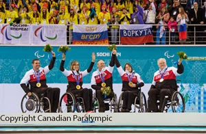 Canadian paralympians celebrating on medal stage.