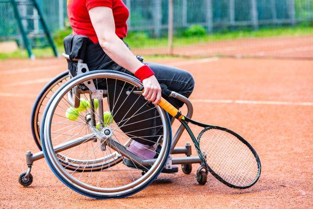 Joueur de tennis en fauteuil roulant sur un terrain en terre battue