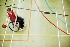 Wheelchair basketball athlete dribbling in a gym.