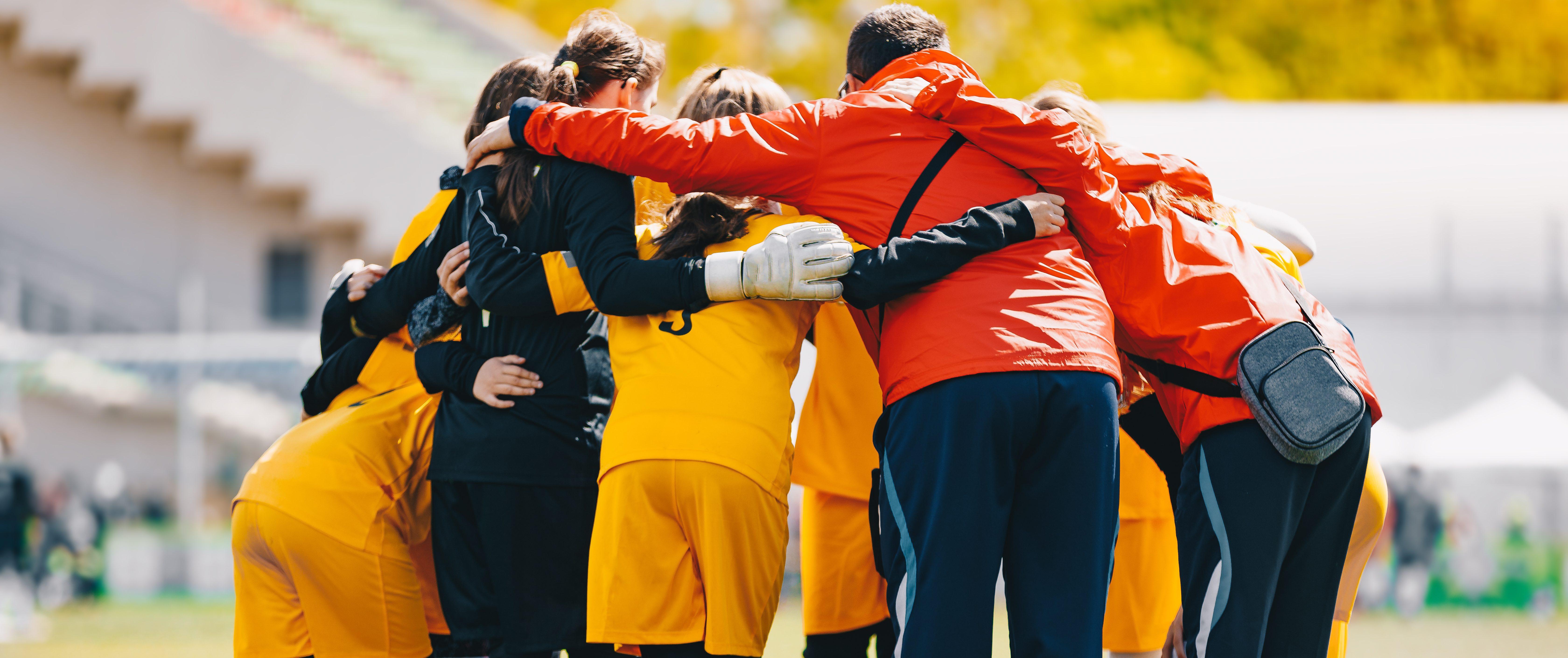 Coach huddled with youth athletes.