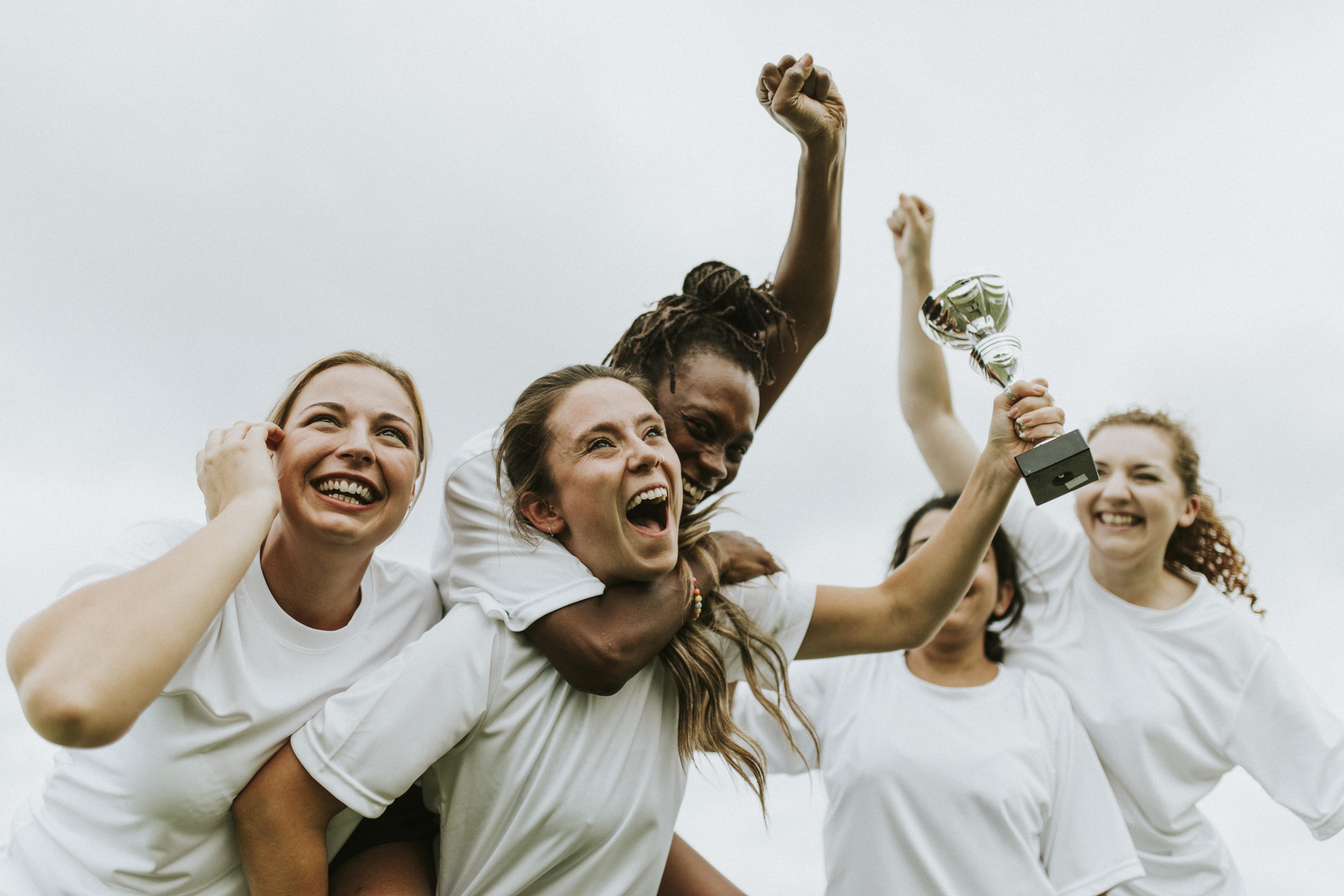 Young female athletes celebrating trophy