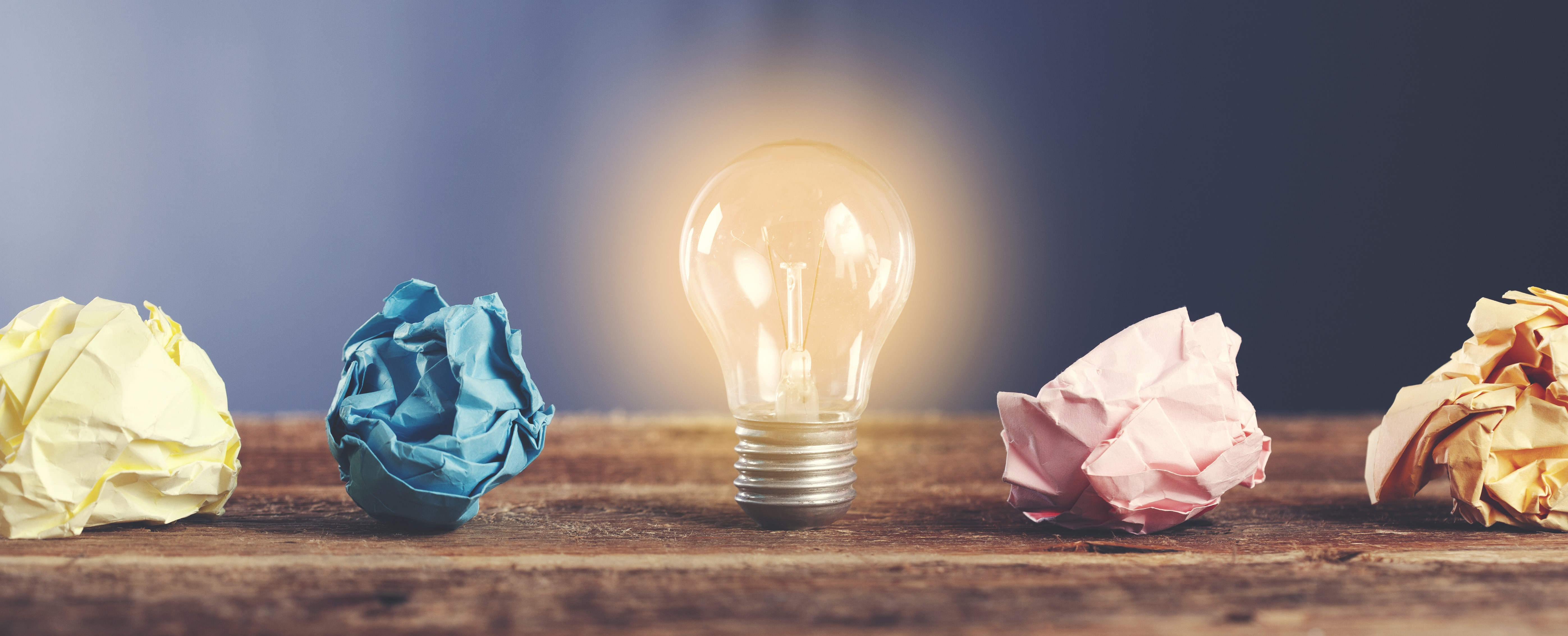 Lightbulb with crumpled paper on wooden desk