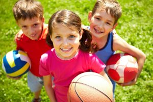 Three smiling kids with an assortment of sports equipment