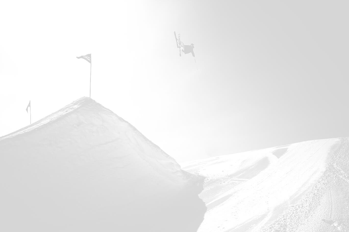 A freestyle skier in the air high above the hill.