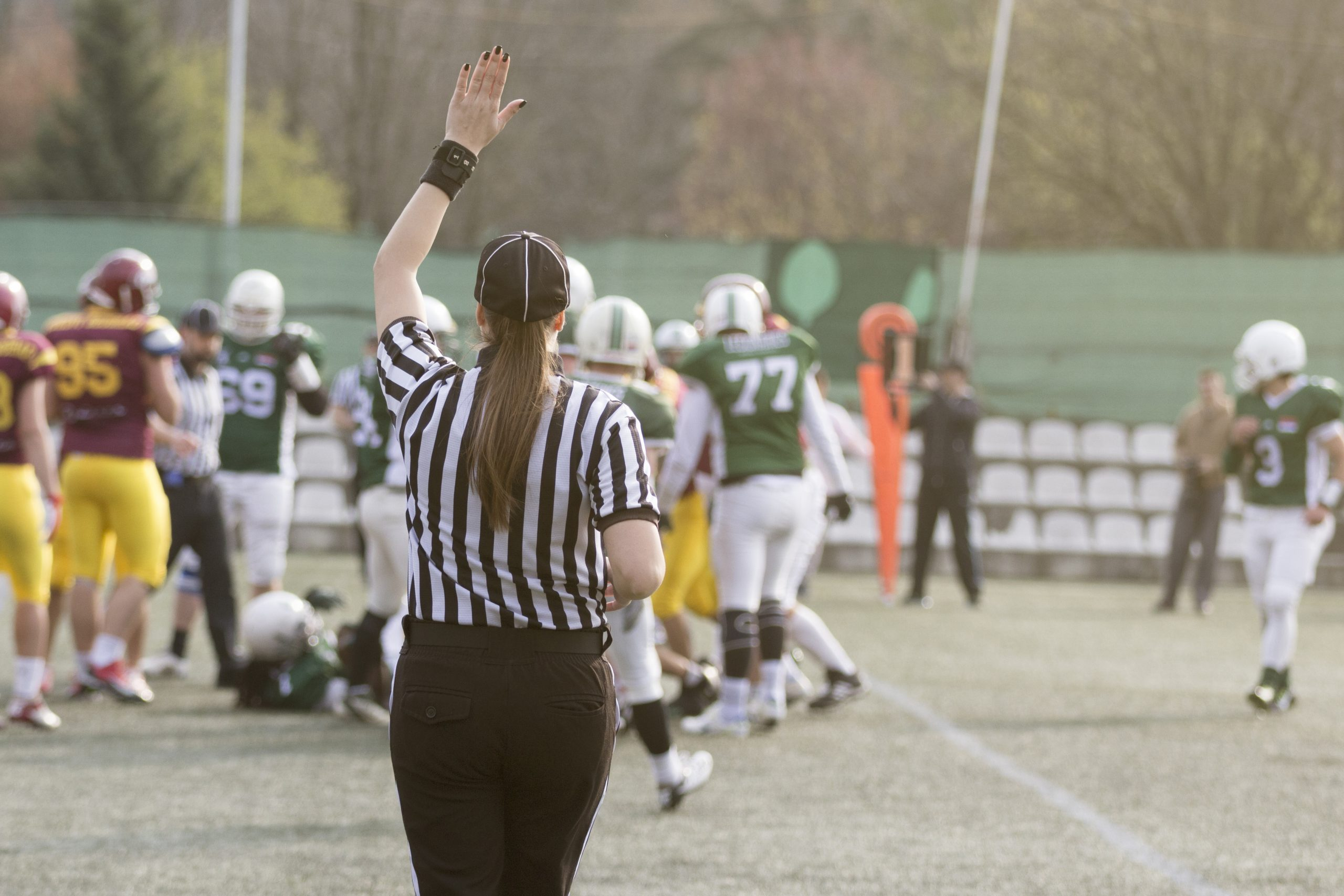 Female football referee giving signals and blurred players in the background
