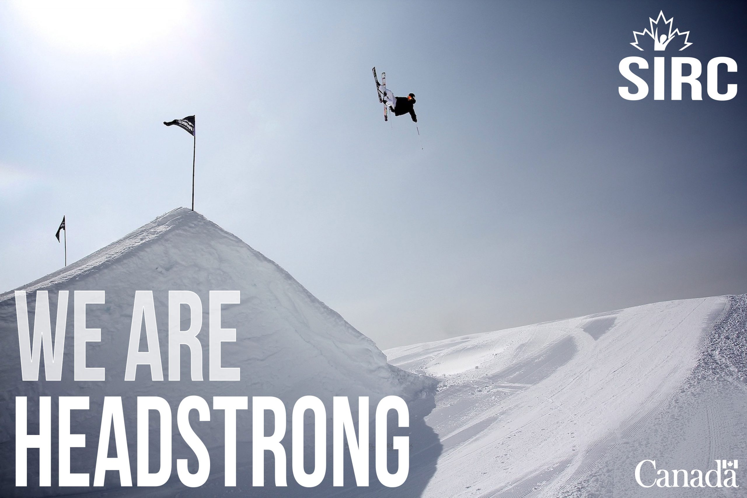 Freestyle skier in the air high above the hill. Text: We are headstrong. SIRC