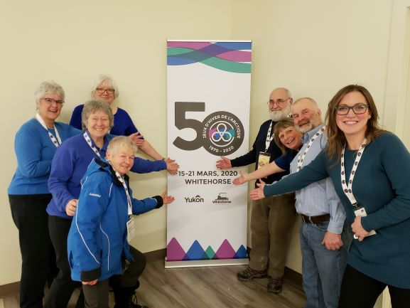 Eight people posing next to the Whitehorse Canada Winter Games