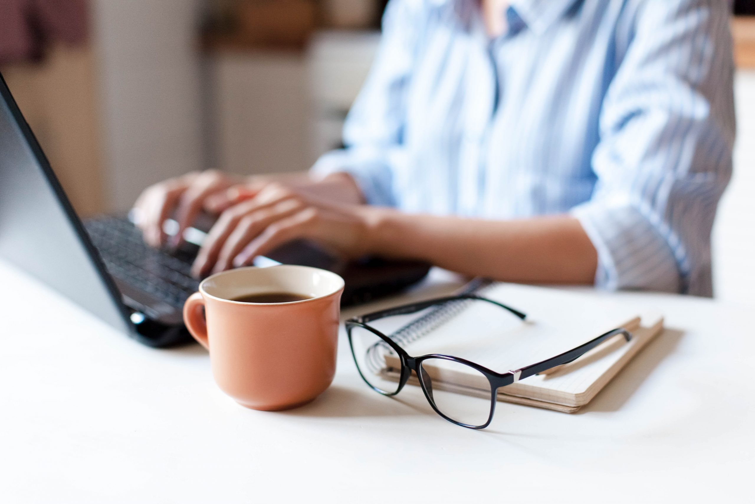 Person sitting at desk typing on a laptop. Coffee, glasses and notepad next to laptop.