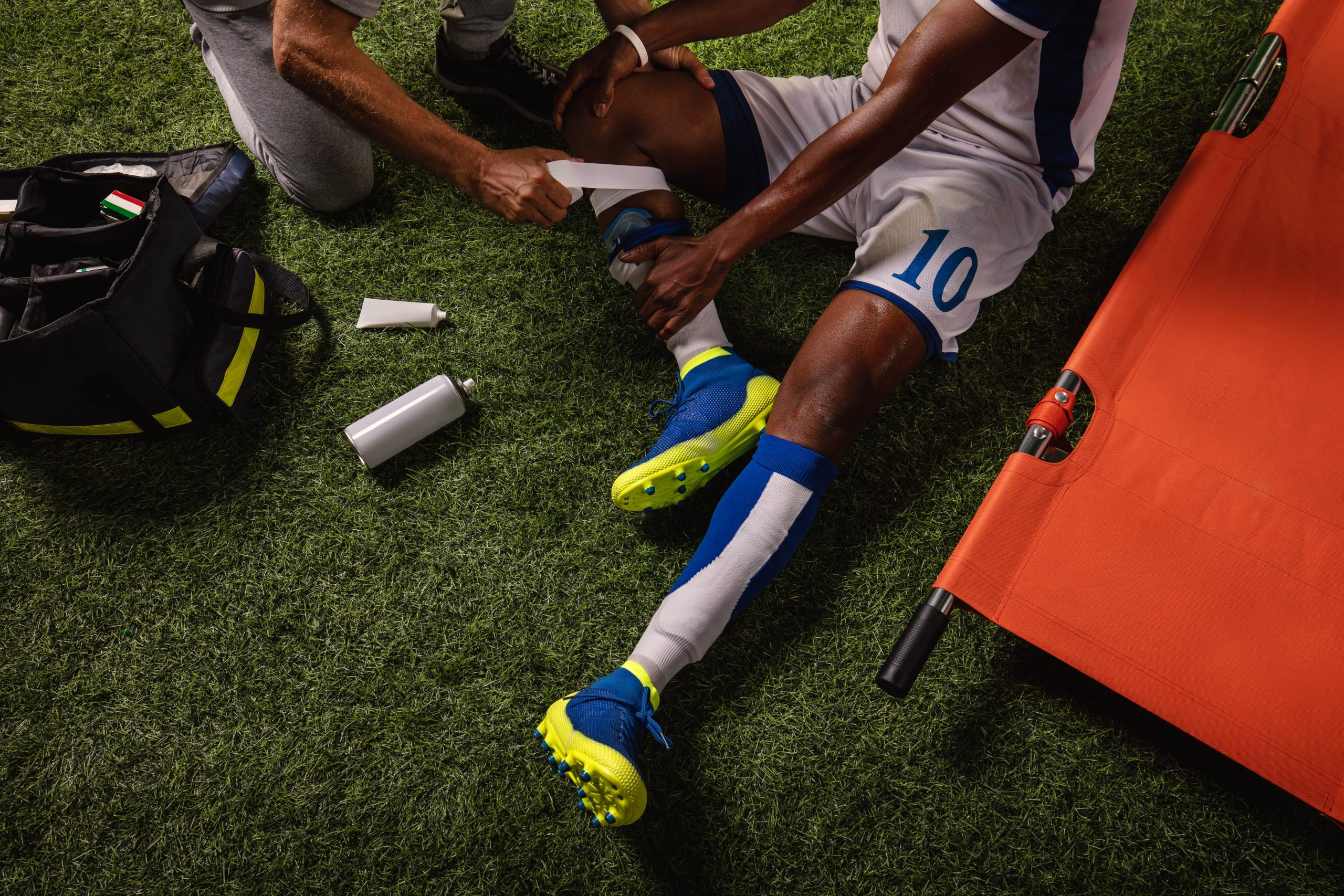 Soccer player injured knee during the game. Sport Doctors provide first aid to player on a professional football field