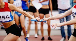 women relay team passing of baton