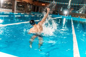 Male swimmer in pool celebrates win
