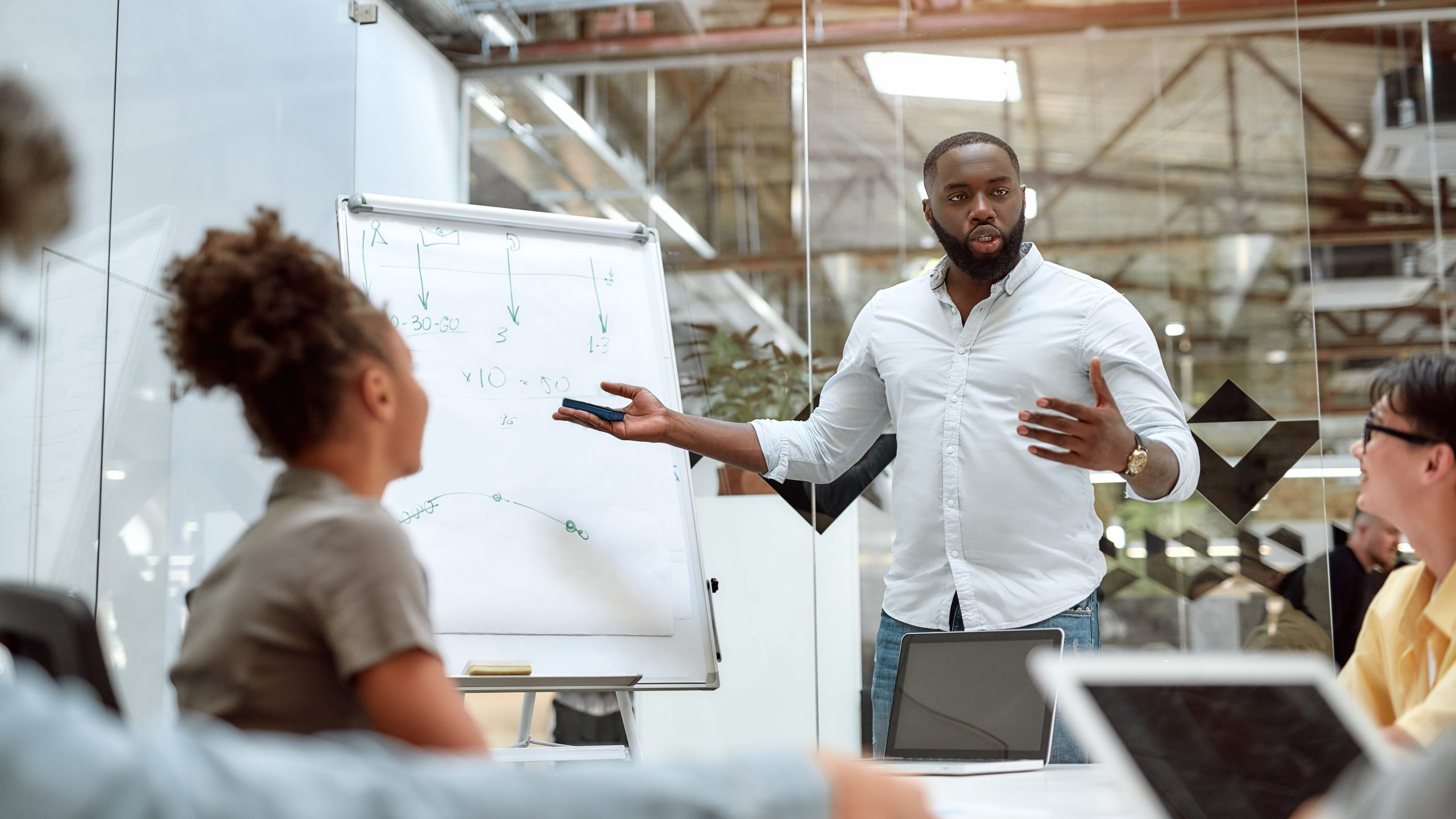 Young afro american businessman pointing at white blackboard and explaining new project to his colleagues while working together in the creative office. Teamwork. Presentation