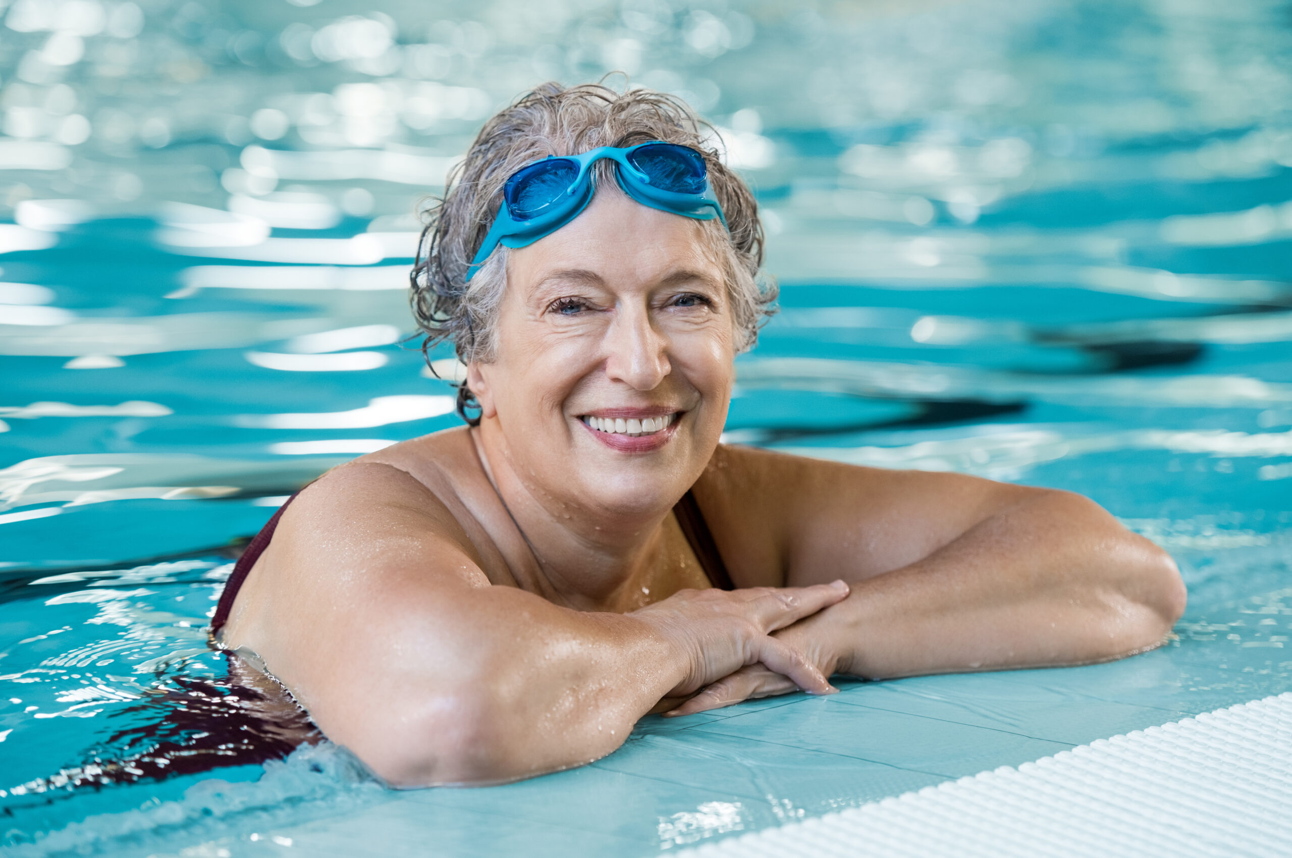 Mature woman wearing swim goggles resting on edge of swimming pool smiling at camera.