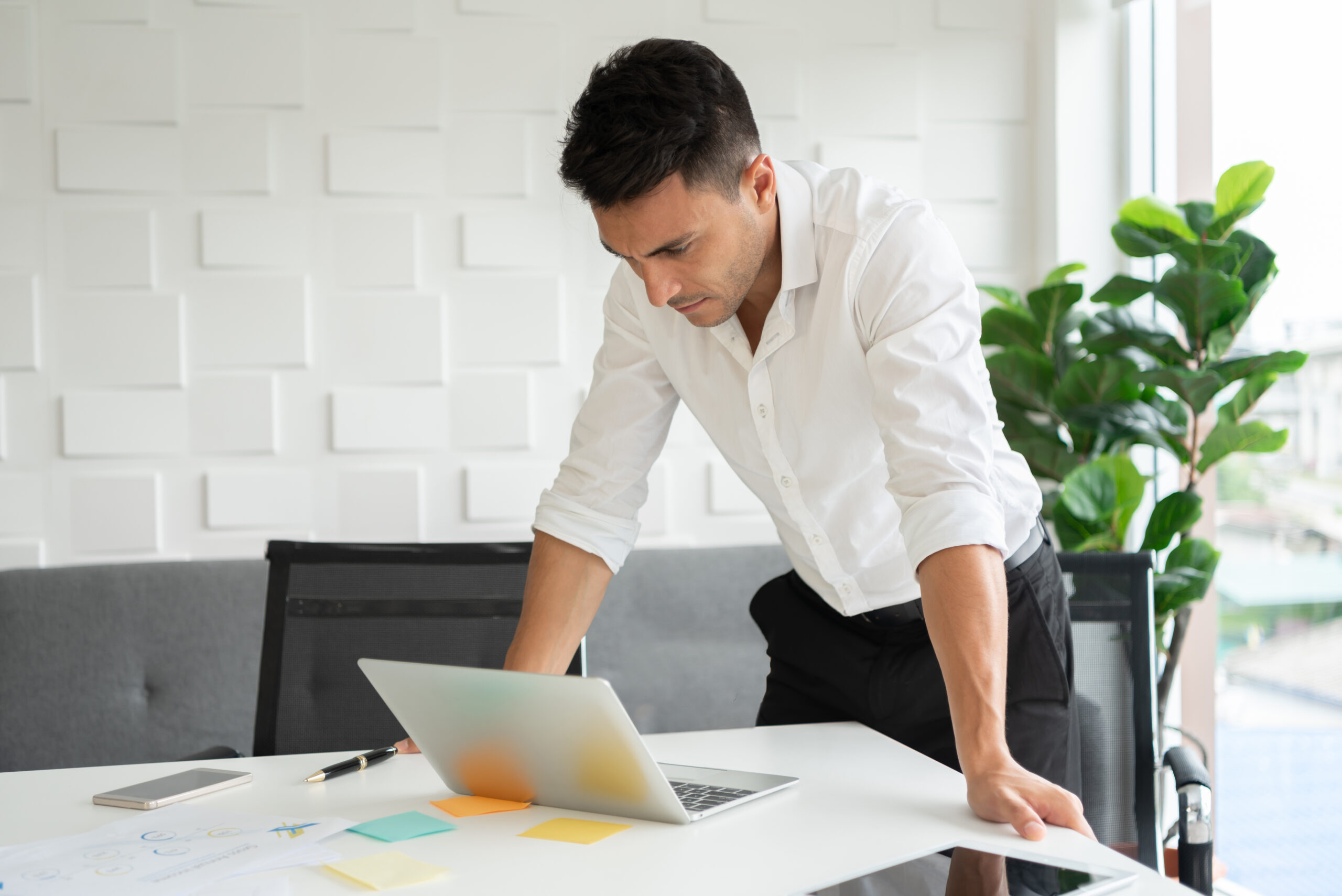 Young businessman is standing with hands on desk, looking at a laptop.