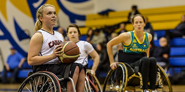 Female basketball para-athlete in wheelchair about to take a shot.