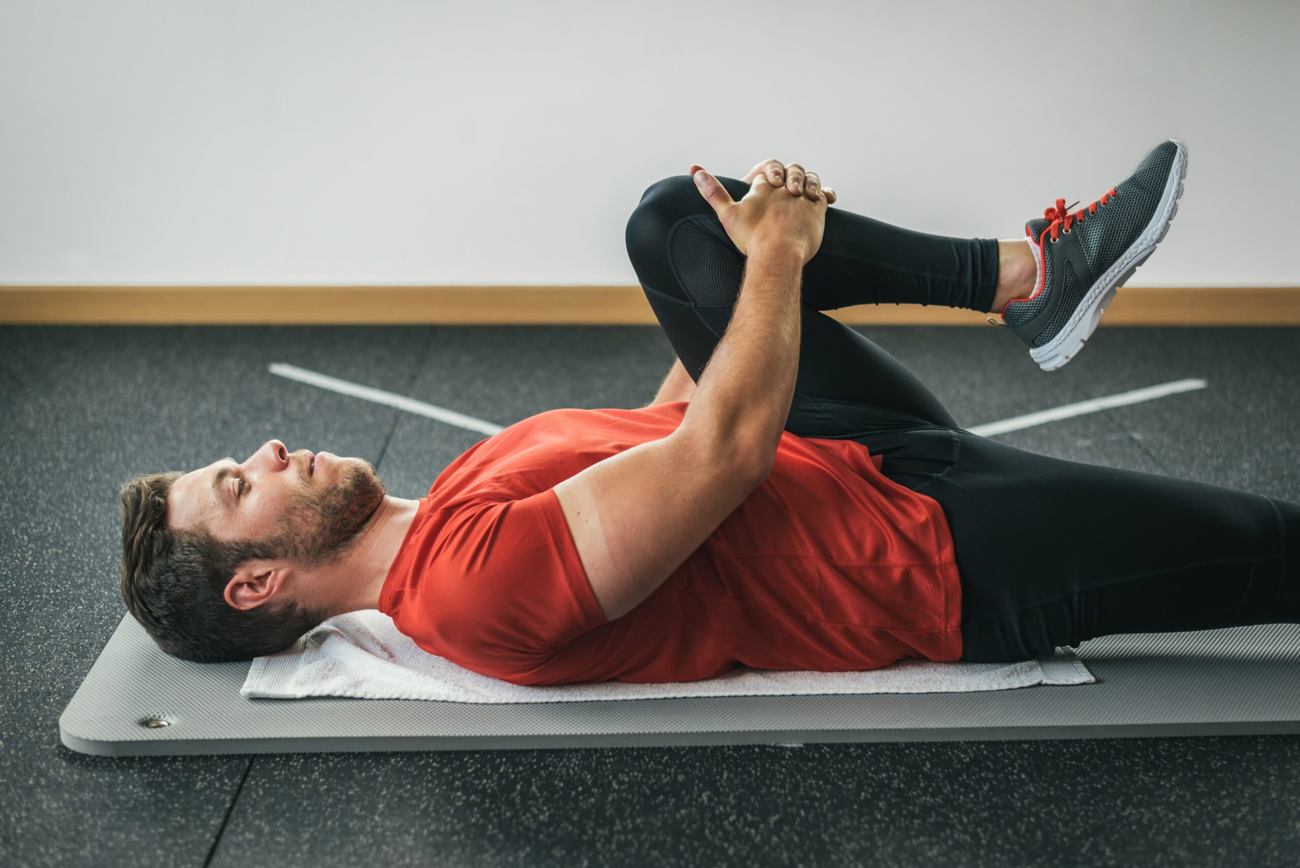 Man laying on yoga mat stretching lower back and leg.