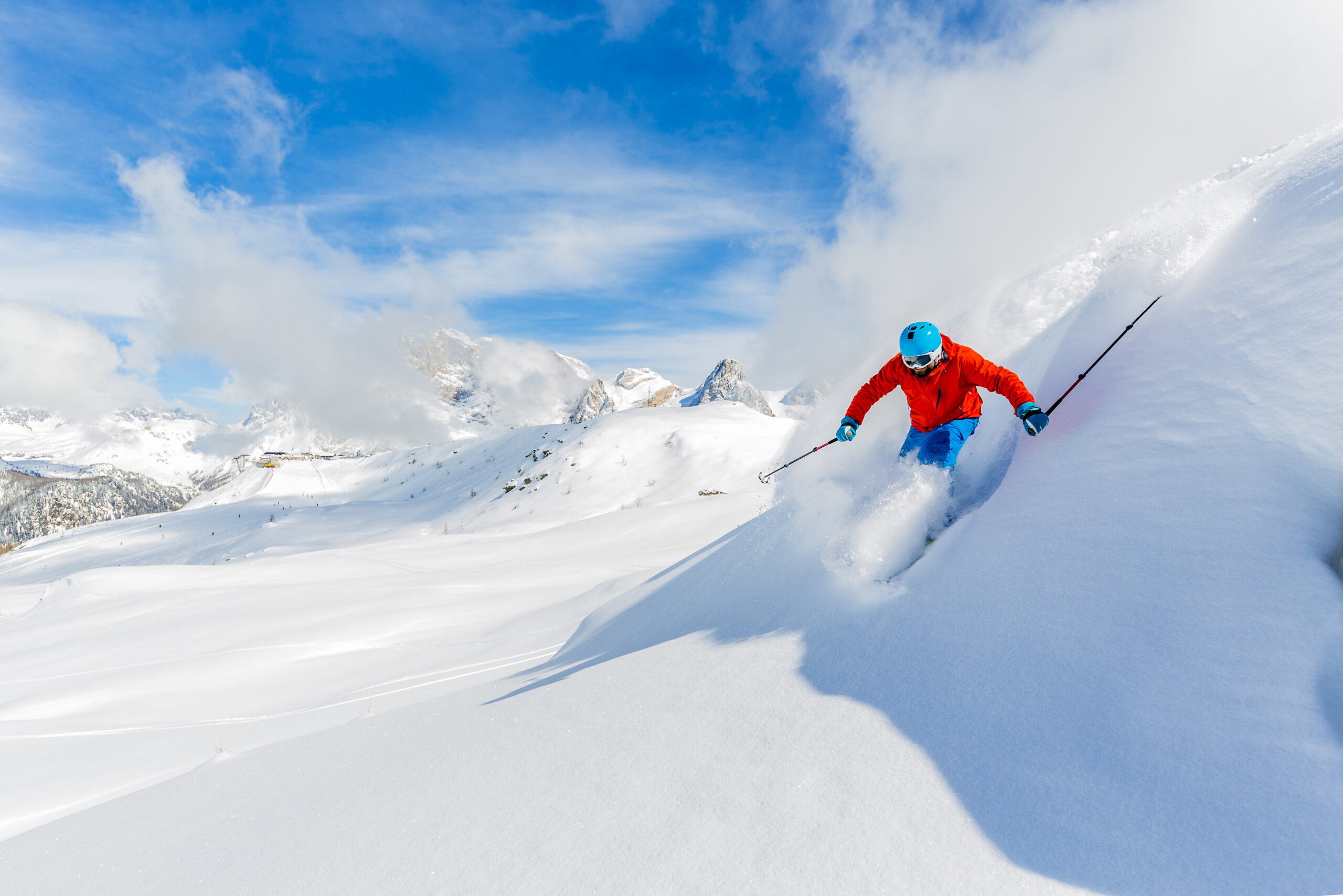 Skier skiing high in mountains in fresh powder snow.