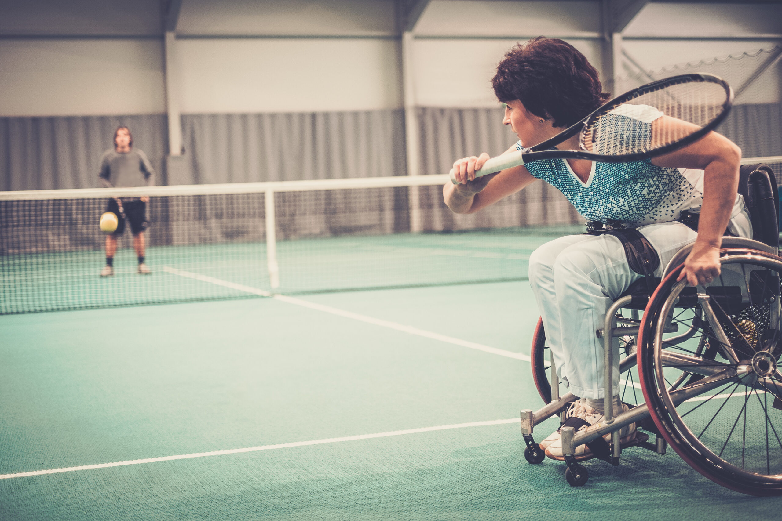 Female para athlete on wheelchair playing tennis on tennis court