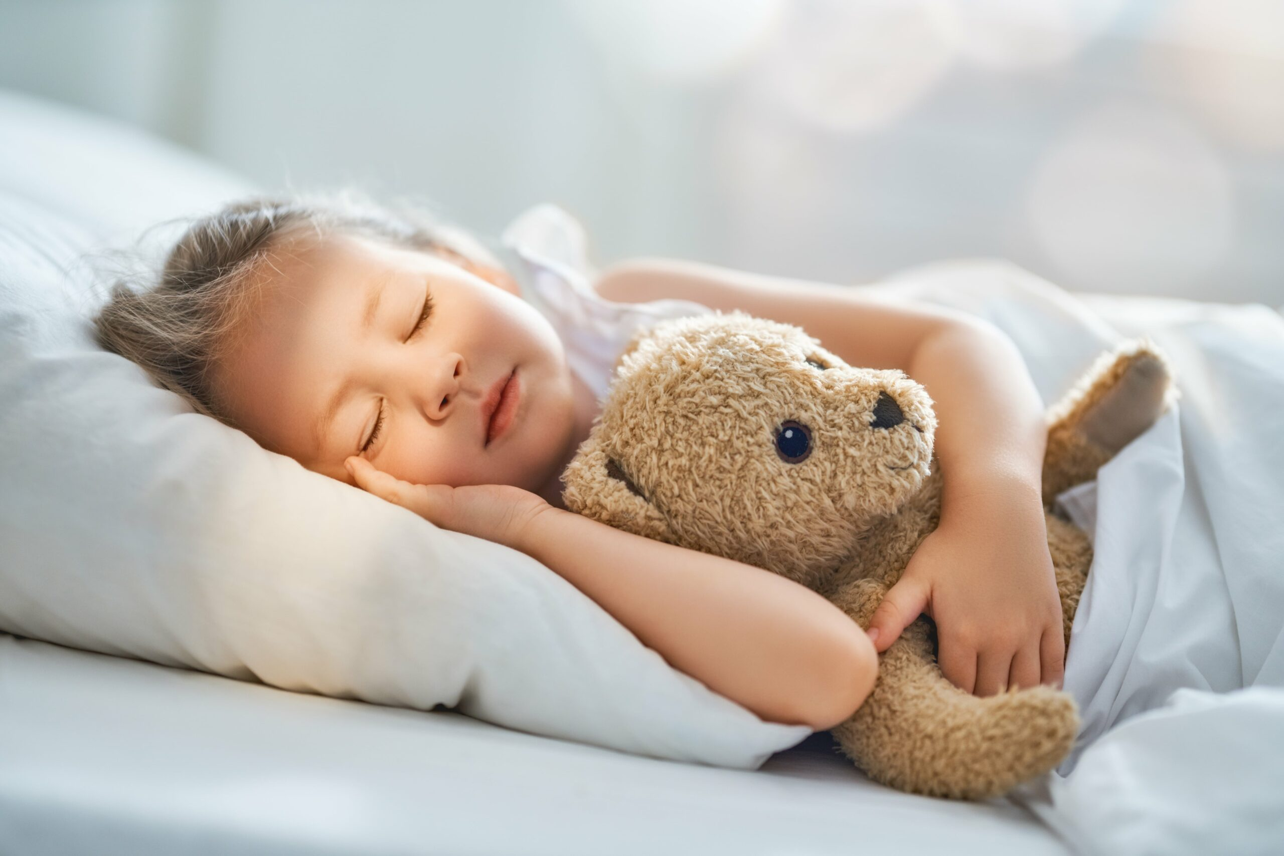 Young girl sleeping with a plush bear.