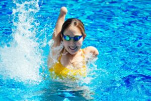 Young female athlete with a disability swimming, happy