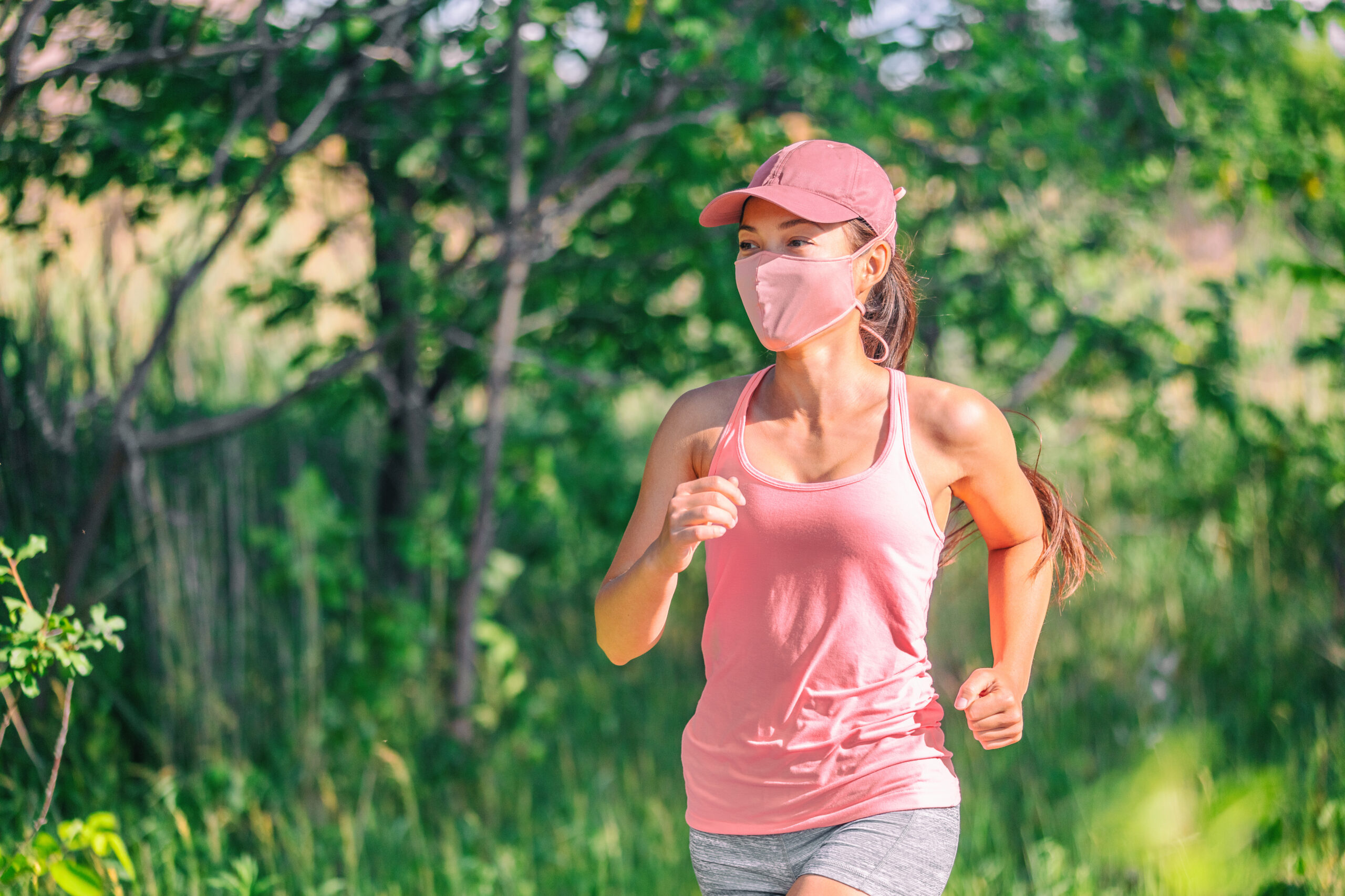Woman running outside wearing a mask