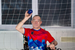 Boccia. A male, person with disability, in wheelchair, playing boccia, throwing a blue ball.