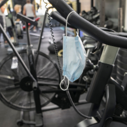 Face-mask hanging off handlebars of an exercise bike in a gym.