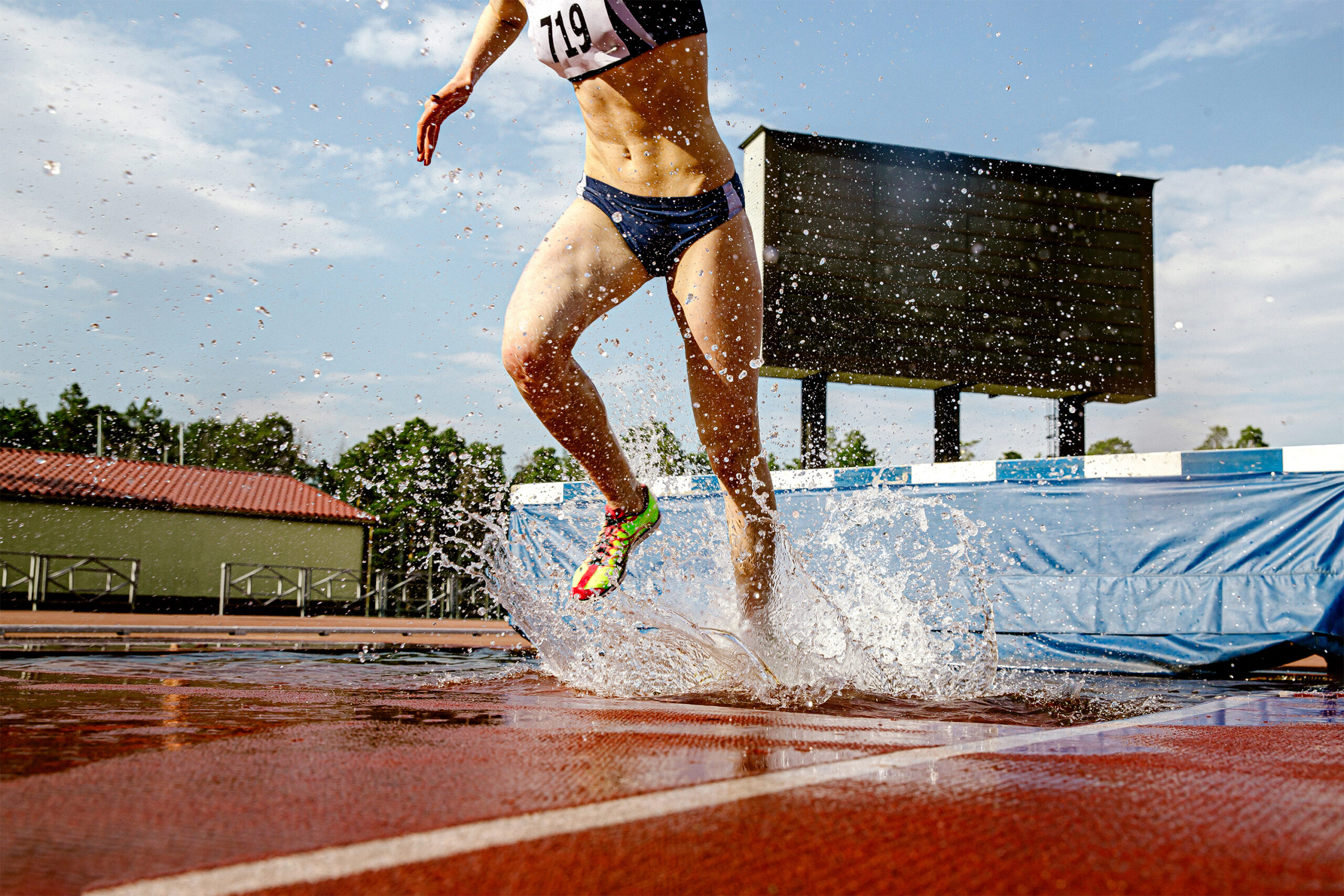 women athlete steeplechaser run pit with water in steeplechase race