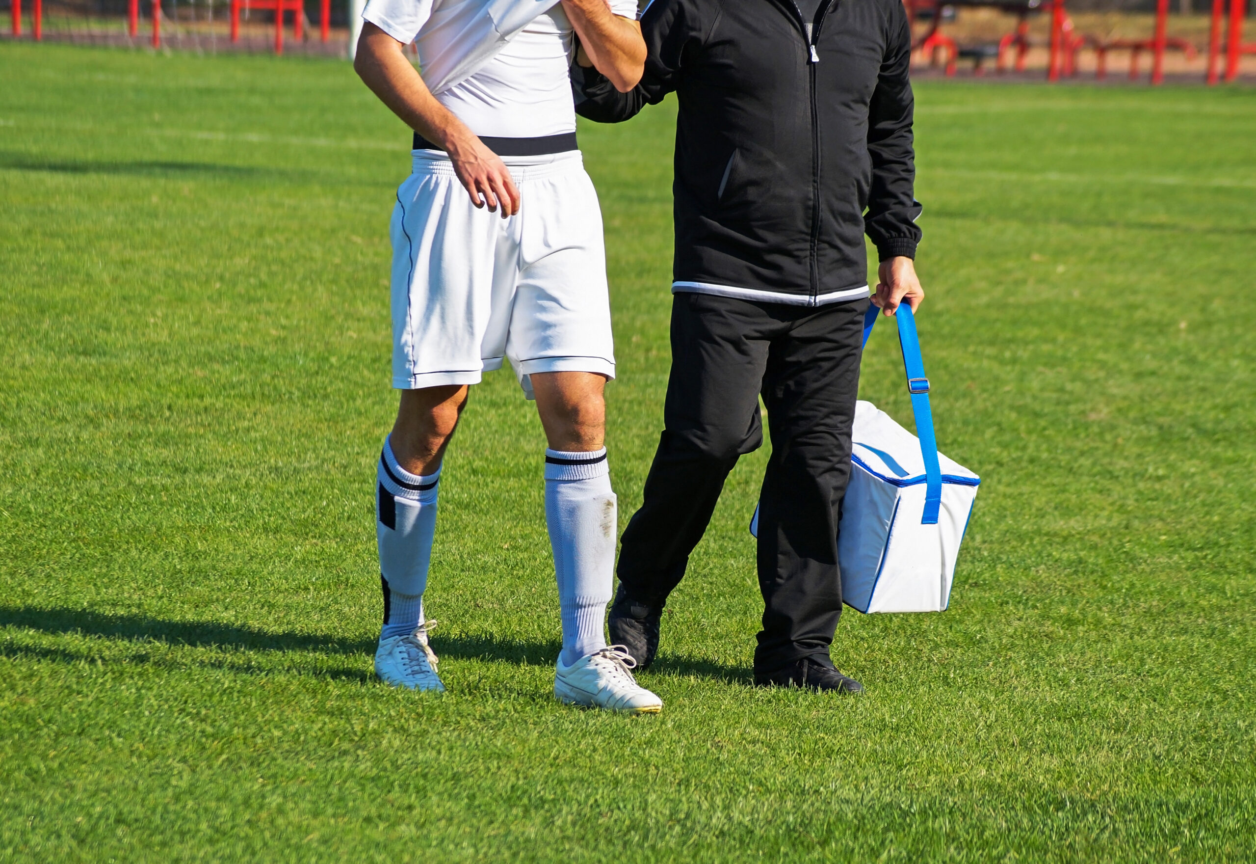 Medic walking with injured soccer player.
