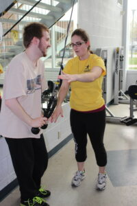 APEX participant and trainer using cable equipment in gym