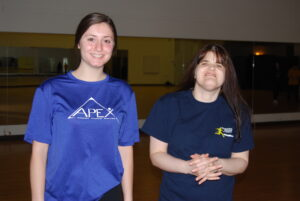 Female APEX participant and trainer standing and smiling together