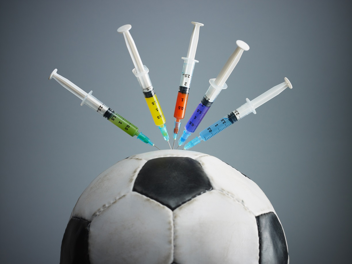 five syringes threaded in soccer ball.