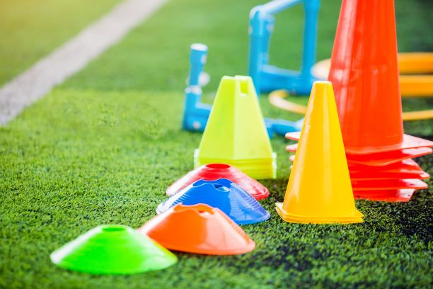 Practice equipment (cones and pylons) sitting on a green playing field