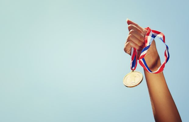 athlete holding medal in air, blue background