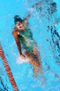 bird eye view of female swimmer doing backstroke in pool