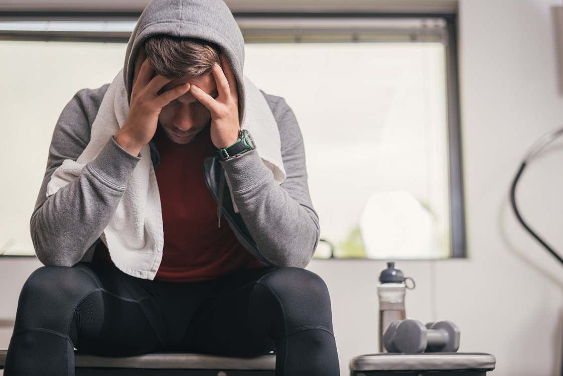 Athlete sitting on gym bench suffering mentally