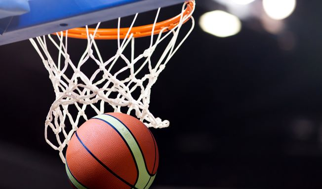 Basketball going into basketball net with a black background