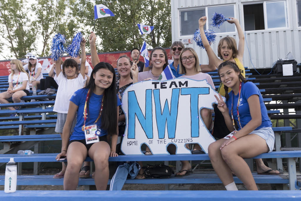 Youth athletes holding a team NWT sign on the bleachers