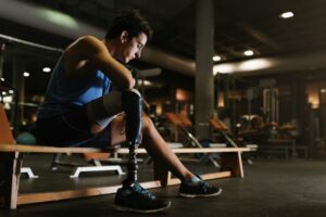 Male athlete with a disability sitting in gym, uncertain