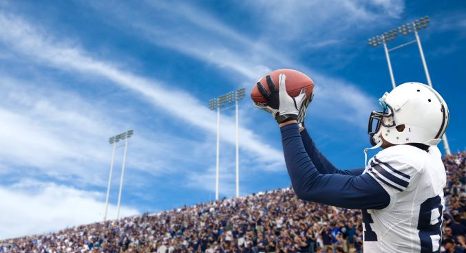 Professional football player making a catch in front of a stadium full of spectators