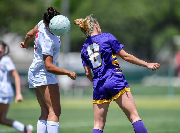 Two girls heading a soccer ball