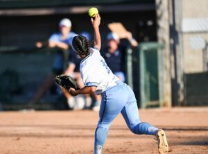 black female varsity athlete throwing a pitch during softball competition