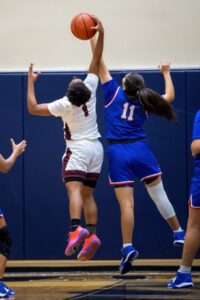 two female varsity basketball players reach for the basketball during a game