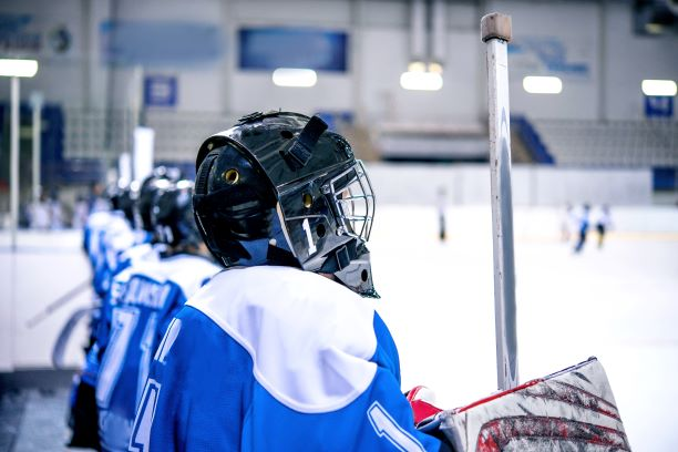 Youth hockey player sitting on bench in blue jersey