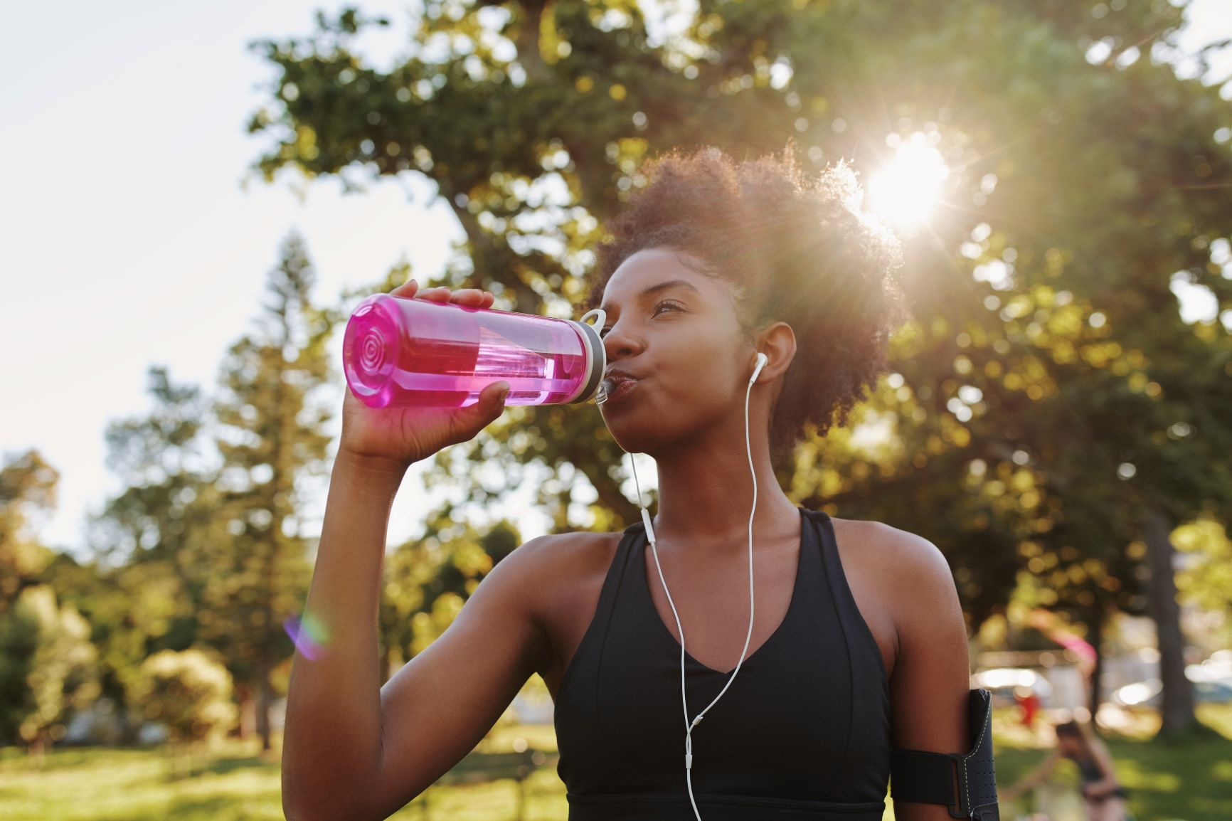 Young african american female fitness athlete listening to music and drinking water after exercising.