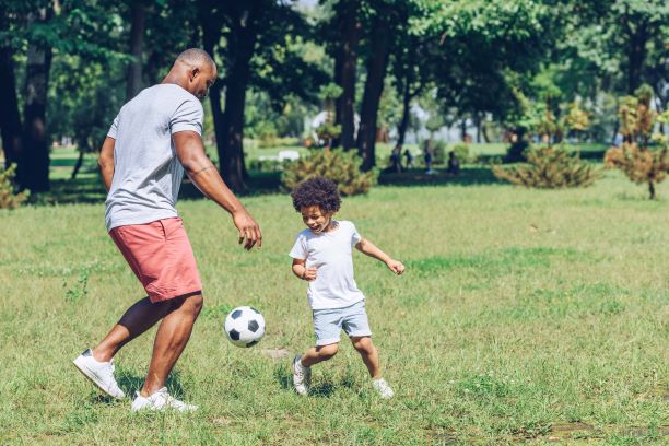 Father and child playing soccer in the park.