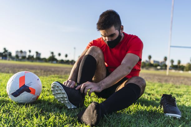 Male soccer player tying cleats and preparing for training outdoors, wearing a mask.