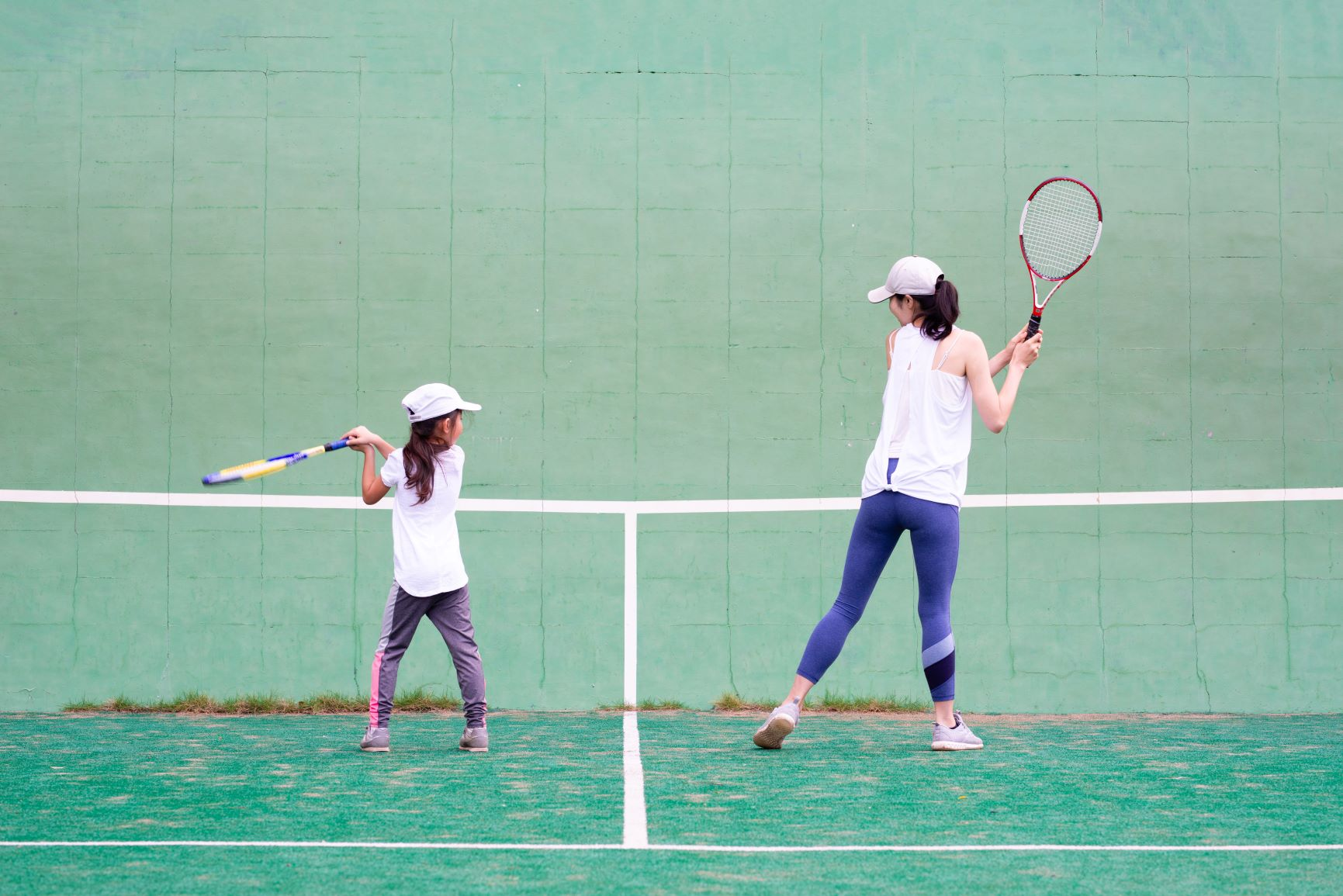 Mom and daughter playing tennis against the wall