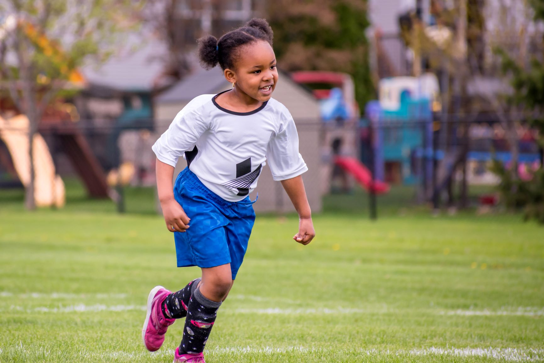 Youth female soccer player running on the field.